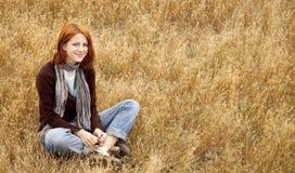 Девушка сидя на желтой траве осени. стоковое изображение