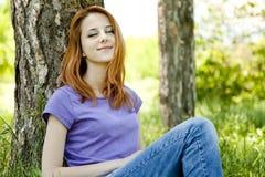 Девушка сидя на зеленой траве на парке. стоковые изображения rf