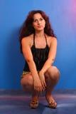 Девушка сидя на корточках в студии Стоковое фото RF