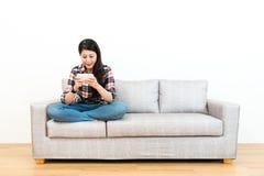 Девушка сидя на кресле софы используя передвижной сотовый телефон стоковые фотографии rf