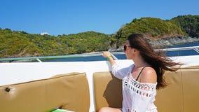 Девушка сидя на носе быстроходного катера Волосы порхая в ветре, стекла перед его глазами стоковое фото rf