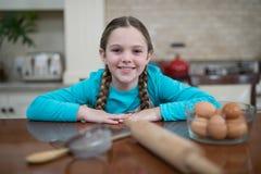 Девушка сидя на таблице в кухне Стоковая Фотография RF
