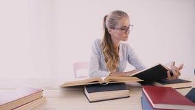 Девушка сидя на таблице в офисе читает много книги сток-видео