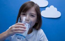 Девушка сидя на таблице, держа стекло молока стоковая фотография