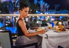 Девушка сидя на таблице ресторана и смотря уныло вниз стоковое изображение