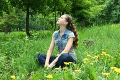 Девушка сидя на траве Стоковая Фотография