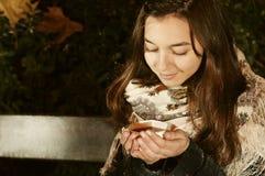 Девушка сидя на banch в парке ночи и принимая чашку чая Стоковое Изображение