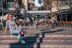 Девушка сидя около серебряного памятника аиста Стоковые Фотографии RF