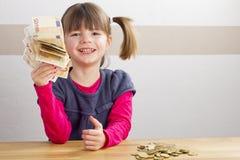 Девушка сидя перед много деньгами Стоковая Фотография