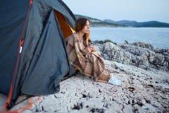 Девушка сидя под шатрами, обернутыми в шотландке, держа чашку душистого чая Стоковая Фотография RF