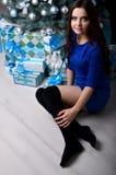 Девушка сидя с подарками под рождественской елкой стоковое фото rf