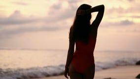 Девушка силуэта во взглядах купальника на заходе солнца и океан на пляже, замедленном движении сток-видео