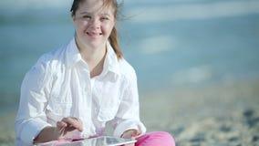 Девушка Синдрома Дауна играя на таблетке сенсорного экрана на пляже видеоматериал