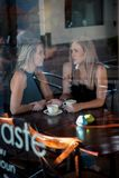Девушка сидела в окне кофейни Стоковое фото RF