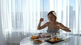 Девушка сидит вниз на кофе таблицы протягивая и выпивая акции видеоматериалы
