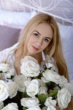 Девушка сидит в кровати с букетом роз Стоковое фото RF