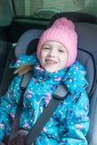 Девушка сидит в стуле малолитражного автомобиля, усмехаясь стоковые фото