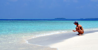Девушка сидит и смотрящ к океану Стоковая Фотография