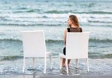 Девушка сидит на белом стуле и смотрит море Очаровательная маленькая девочка сидит на предпосылке моря Стоковые Изображения