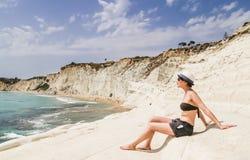 Девушка сидит на вызванном наклоне белой скалы стоковая фотография