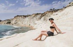 Девушка сидит на вызванном наклоне белой скалы dei Turchi Scala стоковые изображения