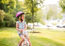 Девушка сидит на ее велосипеде в парке города Стоковое Изображение RF