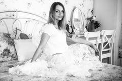 Девушка сидит на кровати Стоковое Изображение RF