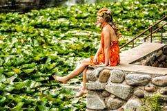 Девушка сидит на пристани смотря озеро с лотосом Стоковые Фото