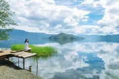 Девушка сидит на расточительствованной платформе смотря камеру Стоковые Изображения