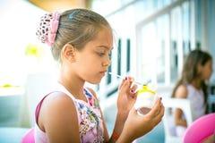 Девушка сидит на таблице и украшает figurine глины Стоковая Фотография RF
