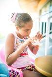 Девушка сидит на таблице и украшает figurine глины Стоковое Изображение