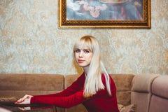 Девушка сидит на таблице Стоковые Фото