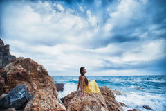 Девушка сидит на утесе на пляже против неба и моря Стоковые Изображения RF