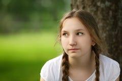 Девушка сидит около дерева в парке Стоковые Фотографии RF