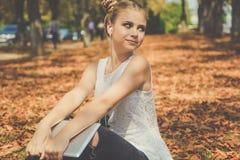 Девушка сидит с цифровой таблеткой внешней Стоковое Фото
