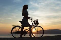 Девушка силуэта с велосипедом Стоковые Фотографии RF