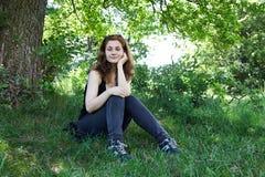 Девушка сидя вниз в природе Стоковые Изображения RF
