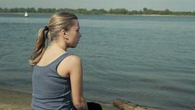 Девушка сидя водой и смотря в сток-видео