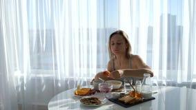 Девушка сидя в белой кухне и ест блинчики видеоматериал