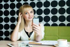 Девушка сидя в кафе держит мобильный телефон стоковая фотография rf