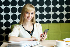 Девушка сидя в кафе держит smartphone стоковое фото rf