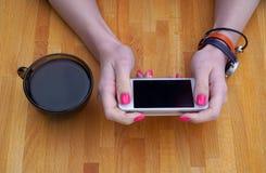 Девушка сидя в кафе таблица и выпивая черный кофе, используя ваш smartphone стоковые фотографии rf