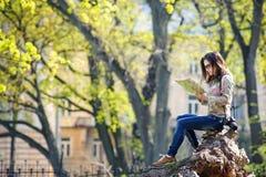 Девушка сидя в парке и читая карту стоковое изображение