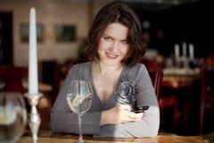 Девушка сидя в ресторане стоковая фотография
