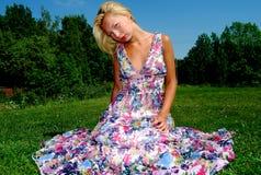 Девушка сидя в траве Стоковое Изображение