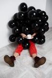 Девушка сидя в черных baloons держа чашку над белой стеной Стоковое Фото