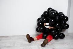 Девушка сидя в черных baloons держа чашку над белой стеной Стоковая Фотография