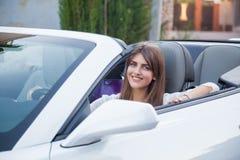 Девушка сидя за колесом белого автомобиля с откидным верхом Стоковая Фотография RF