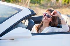 Девушка сидя за колесом белого автомобиля с откидным верхом Стоковое Изображение