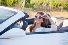 Девушка сидя за колесом белого автомобиля с откидным верхом Стоковое фото RF